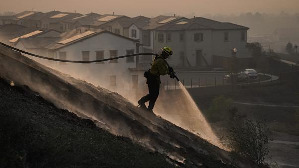 Firefighter Tylor Gilbert puts out hotspots while battling the Silverado Fire, Monday, Oct. 26, 2020, in Irvine, California, USA.