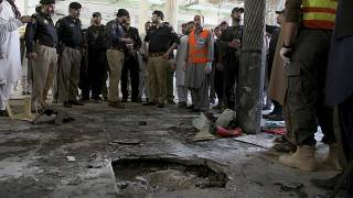 Police officers examine the site of bomb explosion in an Islamic seminary in Peshawar, Pakistan, Tuesday, Oct. 27, 2020.