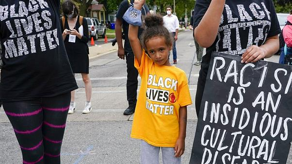 Six-year-old Deja holds her hand in the air during a Black Lives Matter protest Tuesday, Sept. 1, 2020, in Kenosha, Wis.