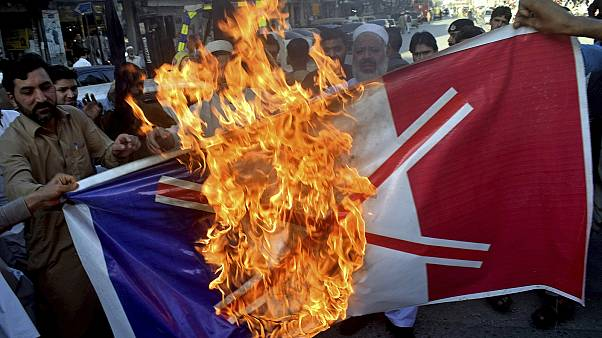 Traders burn burn a French flag during a protest against the publishing of caricatures of the Prophet Muhammad in Peshawar, Pakistan, on Monday, October 26, 2020.