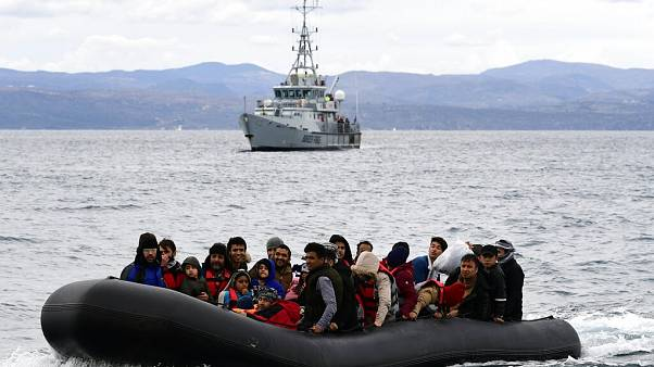 Migrants arrive with a dinghy accompanied by a Frontex vessel at the village of Skala Sikaminias