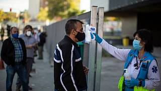 A Madrid Emergency Service (SUMMA) health worker checks the temperature of a man prior to a rapid antigen test for COVID-19 in Madrid. Oct 27, 2020