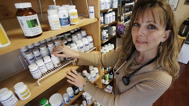 الممرضة كريستين أندرس تتفحص بعض الفيتامينات والمكملات الغذائية في مركزها الصحي في بتسبيرغ.