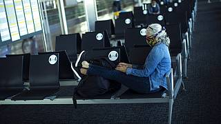A passenger, wearing a face mask to protect against the spread of coronavirus, sits before boarding her flight at the Zaventem international airport