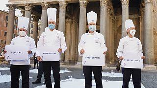 """Cozinheiros em protesto em frente ao panteão de Roma com as mensagem """"#cozinheiros"""", """"#estamos por terra"""", """"#restaurantes"""" e """"#inovação"""""""
