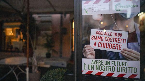 """Une affiche sur laquelle est noté """"aujourd'hui, nous sommes obligés de fermer à 18 heures""""  sur la porte d'un restaurant de Rome, Italie, le 28 octobre 2020"""