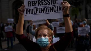 """متظاهرة كتالونية ترفع لافتة كتب عليها """"أوقفوا القمع"""" بعد اعتقال 21 شخصاً يشبته بتورطهم بهدر المال العام"""
