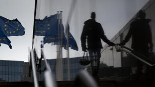 A man carries a cycling helmet and walks by EU flags as he is reflected in a marble staircase outside EU headquarters in Brussels, Wednesday, Oct. 28, 2020.