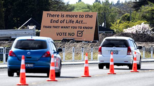 """In this Oct. 16, 2020, file photo, cars are driven past a billboard urging voters to vote """"No"""" against euthanasia in Christchurch, New Zealand"""