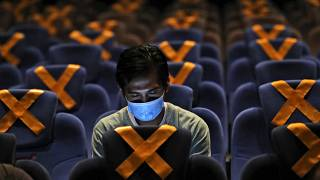 رجل يراقب هاتفه داخل قاعة سينما في العاصمة الاندونيسية جاكارتا حيث وضعت على المقاعد علامات التباعد الاجتماعي. 2020/10/23