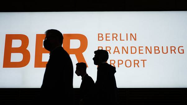 People walk in front of a sign of the new Berlin-Brandenburg-Airport 'Willy Brandt' in inside the Terminal 1, 27 Oct 2020