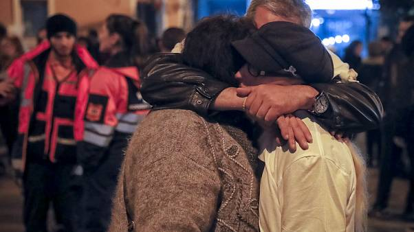 People hug outside the Colectiv nightclub, the scene of a fire which killed 64, during a commemoration in Bucharest, Romania, Friday, Oct. 27, 2017.