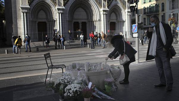 A woman lights a candles in front of the Notre Dame church, in Nice, France, Friday, Oct. 30, 2020.