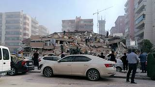 People work on a collapsed building, in Izmir, Turkey, Friday, Oct. 30, 2020, after a strong earthquake in the Aegean Sea