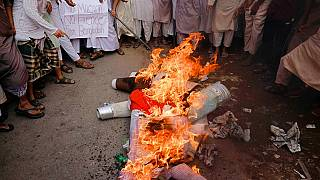 Supporters of Islami Oikya Jote, an Islamist political party, burn an effigy representing French President Emmanuel Macron during a protest in Dhaka, Bangladesh