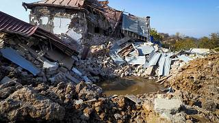A bomb crater near a house destroyed by shelling by Azerbaijan's forces during a military conflict in Shushi, outside Stepanakert, the separatist region of Nagorno-Karabakh