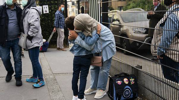 A woman, wearing a face mask to fight against the spread of the coronavirus, hugs her child before entering the Heembeek primary school during the first day of classes in Brus