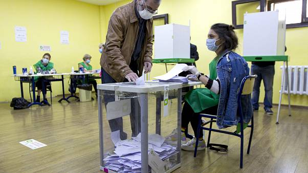 A man wearing a face mask to help curb the spread of the coronavirus, casts his ballot at a polling station during the parliamentary elections in Tbilisi, Georgia, Saturday, O