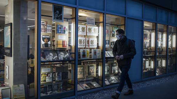 A masked man walks by a bookstore in Paris, Thursday October 29, 2020.