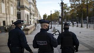 FILE - Police officers patrolling on the Champs Elysees avenue in Paris last month.