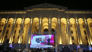 Supporters of Georgian ex-President Mikheil Saakashvili's United National Movement watch his address on a big screen in front of the Parliament's building after the parliament