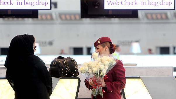A Qatar Airways employee greets a Qatari passenger with flowers on the occasion of the opening of the new Hamad International Airport in Doha, Qatar, Tuesday, May 27, 2014