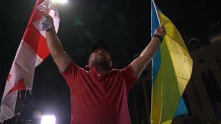Un partidario de la oposición sostiene una bandera de Georgia y otra de Ucrania