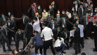 Pro-establishment politician, Starry Lee, center, speaks as pan-democratic legislators scuffle with security guards and pro-China legislators in Hong Kong on May 8, 2020.
