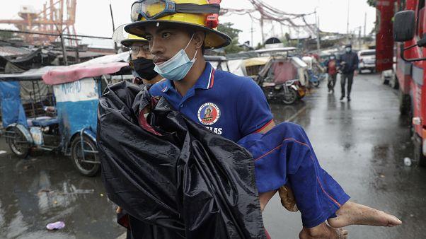 Ein Retter in einem Küstenvorort von Manila bringt ein Kind in Sicherheit