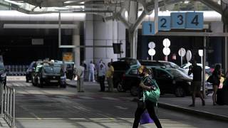 A woman wearing a face mask walks outside Lisbon's airport while in the background taxi drivers stand idle waiting for passengers, Friday, Sept. 11, 2020. Portugal