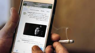 A man reads Saudi news on Twitter fronted by a picture of the prominent bodyguard to Saudi Arabia's King Salman Maj. Gen. Abdulaziz al-Fagham, at a coffee shop, in Jiddah