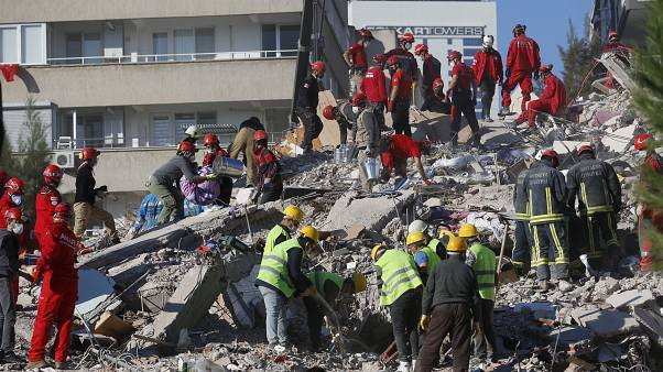 Members of rescue services search for survivors in the debris of a collapsed building in Izmir, Turkey, Saturday, Oct. 31, 2020