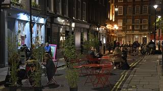 People dine outside on a street in central London, Saturday, Oct. 31, 2020.