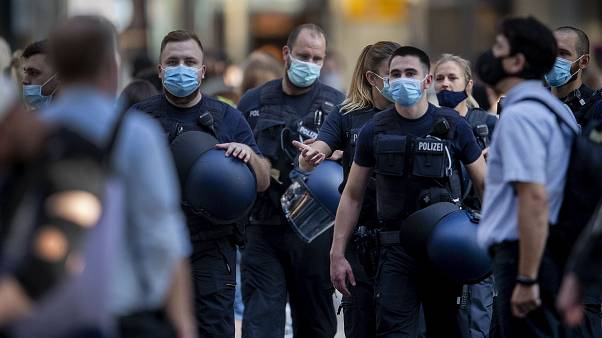 German police officers wear face mask as they walk through the central train station in Frankfurt, Germany, Wednesday, July 22, 2020.