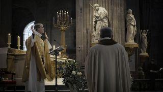 Priest Henri de La Hougue, left, celebrates the All Saints Day mass in Saint-Sulpice church, in Paris, Sunday, Nov. 1, 2020.