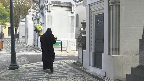 Woman passing by carrying flowers in Lisbon