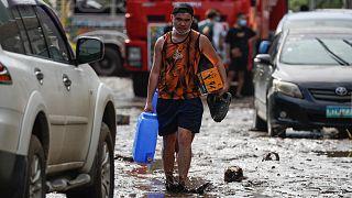 Filipinlerin Batangas eyaletinde, Goni Tayfunun neden olduğu sel sularının ardından çamurla kaplı bir yolda yürüyen köy sakini