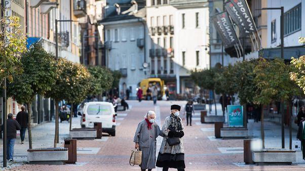 Maszkot viselő emberek sétálnak a Ticino tartományban található Bellinzonában 2020. október 27-én