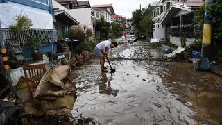 A resident shovels mud from a neighbourhood street following flooding in Batangas City.