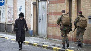 رجل من الجالية اليهودية يسير بجوار جنود بلجيكيين أثناء قيامهم بدورية في أنتويرب، بلجيكا /24 يناير-2015.
