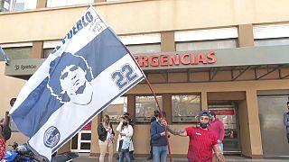 Un hincha ondea una bandera de Maradona a la entrada del hospital de La Plata
