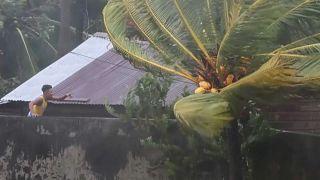 Un joven nicaragüense se asoma al exterior de su vivienda para comprobar el estado de la techumbre en pleno huracán