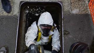 Un miembro de la policía científica sube por la alcantarilla utilizada por los ladrones para escapar