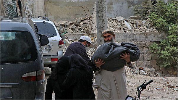 رجل يحمل جثة طفل قضى في القصف على إدلب