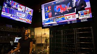 Bartender Sam Schilke watches election results on television at a bar and grill Tuesday, Nov. 3, 2020, in Portland, Ore. (AP Photo/Paula Bronstein)