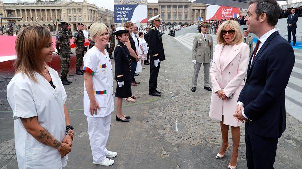 Le ministre français de la santé et Brigitte Macron saluent le personnel de santé lors du défilé militaire du 14 juillet 2020 à Paris.