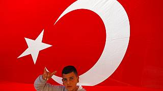 A youth flashes a hand gesture representing the Turkish far-right gray wolves organisation