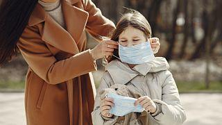 Çocuğuna maske takan bir anne