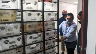 Electoral workers are seen during the vote-by-mail ballot scanning process