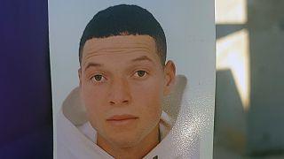 ياسين عيساوي يحمل صورة شقيقه إبراهيم عيساوي